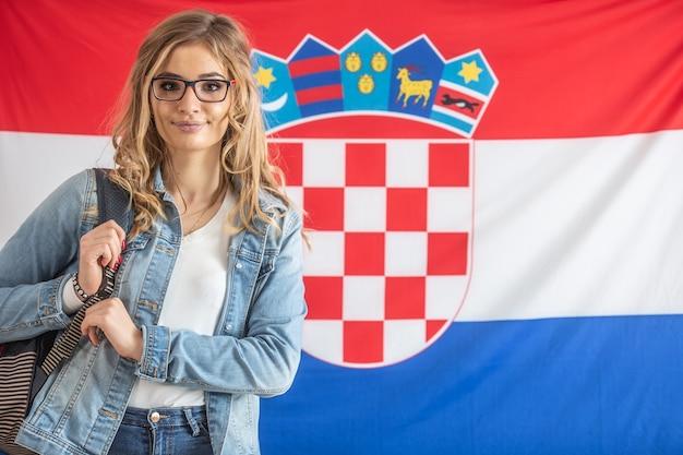Lo studente croato con gli occhiali si trova di fronte alla bandiera della croazia.