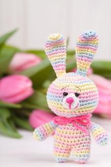Coniglio all'uncinetto sullo sfondo di delicati tulipani rosa.