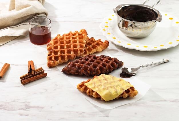 Croffle croisant waffle con vari condimenti, formaggio, cioccolato, zucchero e cannella. croffle è il cibo di strada virale dalla corea. copia spazio
