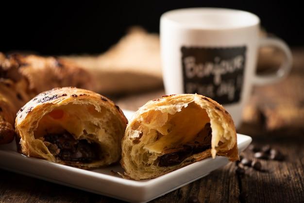Primo piano croissant in legno con primo piano caffè