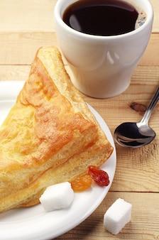 Croissant e caffè su tavola di legno
