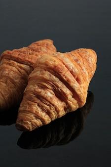 Croissant isolato su sfondo nero, concetto di panetteria francese, una pasta sfoglia