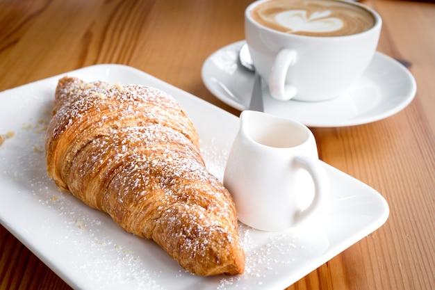 Un croissant e latte è una deliziosa colazione su un pavimento di legno.