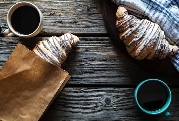 Croissant in un sacchetto di carta con una tazza di caffè. colazione, merenda,