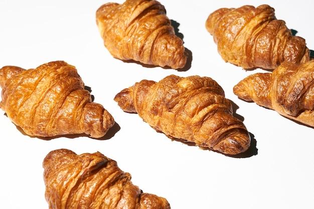 Motivo a croissant con luce dura su sfondo bianco. tanti croissant diversi