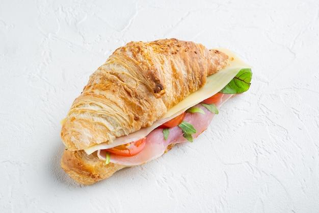 Insieme del panino del croissant, su fondo di pietra bianco, con lo spazio della copia per testo