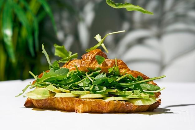 Panino croissant con rucola, avocado, cetriolo. luce forte. sfondo bianco
