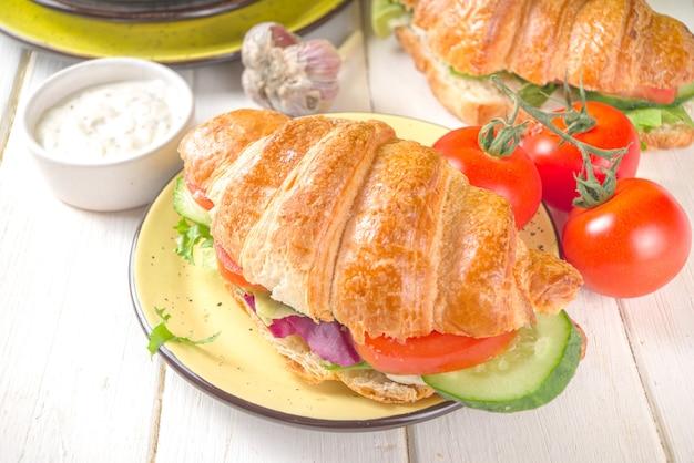 Panino croissant con verdure fresche - lattuga, pomodori, cetrioli. estate dieta vitaminica o spuntino primaverile, colazione.