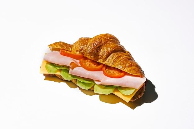 Panino croissant con mortadella, formaggio, rucola e uova strapazzate. luce forte. sfondo bianco