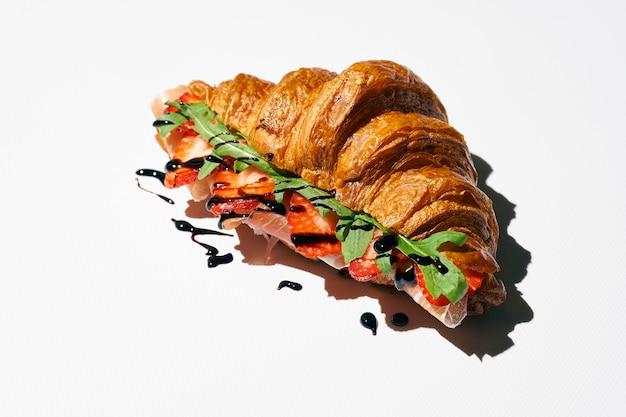 Panino croissant con prosciutto, fragole, rucola e salsa balsamica. luce forte. sfondo bianco