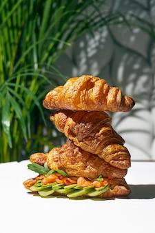 Panino croissant con salmone, rucola e avocado. luce forte. sfondo bianco
