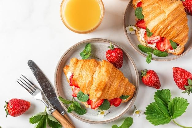 Panini croissant con fragole fresche, menta e crema di formaggio in un piatto con succo d'arancia per una gustosa colazione sul tavolo bianco
