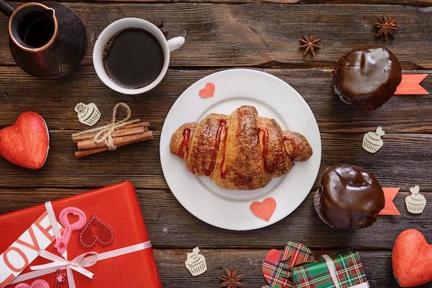 Croissant servito per colazione vacanza sul tavolo di legno scuro con scatole regalo e tazza di caffè
