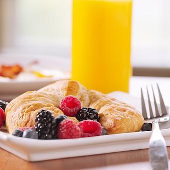 Croissant servito con frutti di bosco e un bicchiere di succo d'arancia
