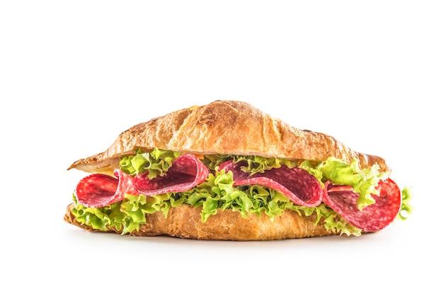 Croissant farcito con insalata di lattuga e salame isolato su sfondo bianco.
