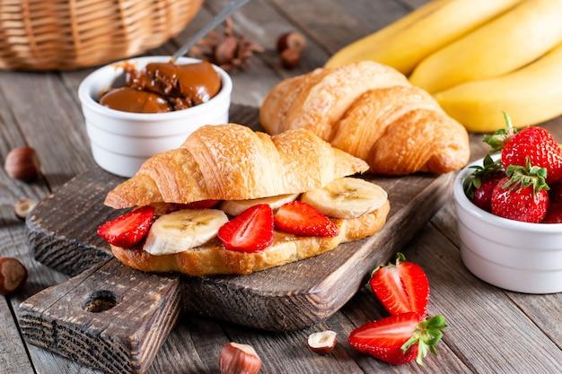 Croissant con banana, burro di arachidi e fragola su tavola di legno