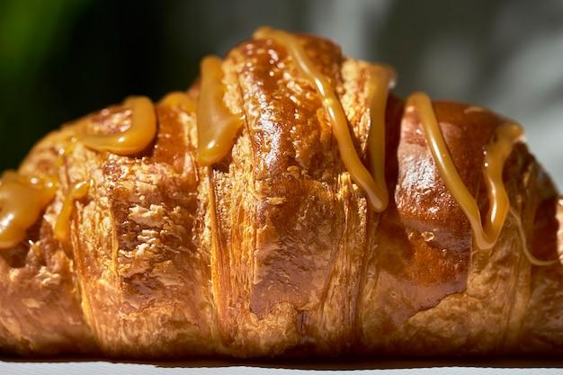 Croissant con caramello e noci. luce forte. sfondo bianco. texture, primo piano, messa a fuoco selettiva