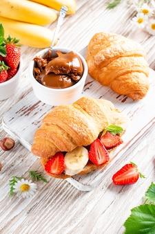 Croissant con burro al cioccolato, banana e fragola su tavola di legno
