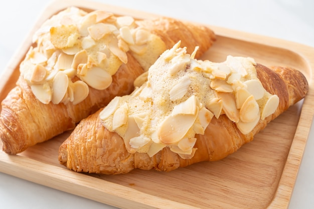 Croissant con panna e mandorle su piastra in legno