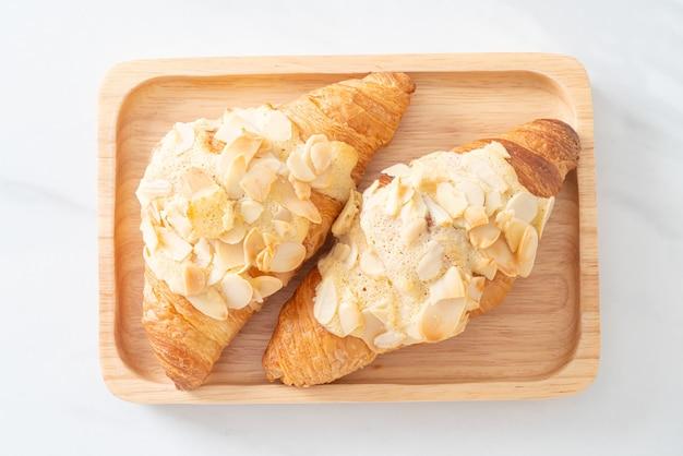 Croissant con crema e mandorle su piastra in legno