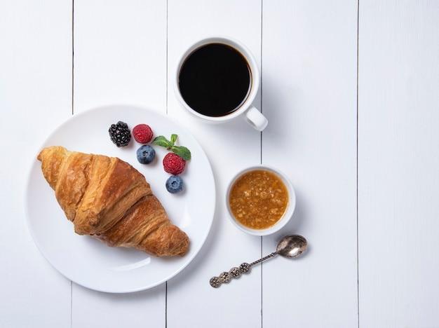 Cornetto con una tazza di caffè e frutti di bosco