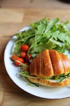 Croissant con uova e pancetta su fondo di legno