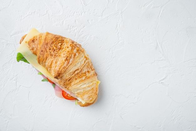Croissant con prosciutto set, su pietra bianca sullo sfondo, vista dall'alto laici piatta, con copia spazio per il testo