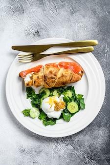Croissant con salmone e ricotta, contorno di insalata con spinaci e uovo