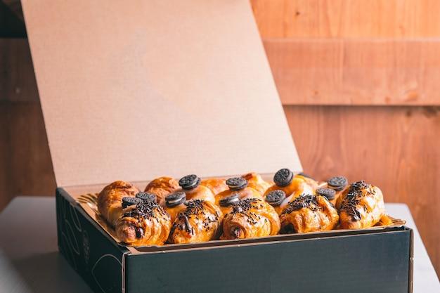 Croissant e ciambelle al cioccolato consegna cibo snack dolci in una scatola