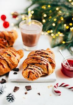 Croissant e bevanda al cacao su un tavolo bianco decorato con decorazioni natalizie