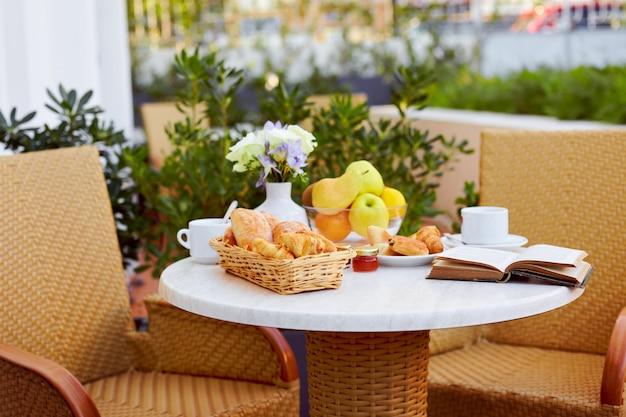 Cornetti, caffè, marmellata e un libro sul tavolo sulla terrazza