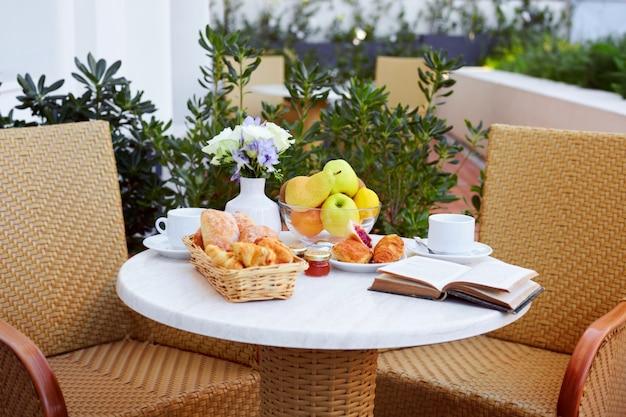 Cornetti, frutta, caffè, marmellata e un libro sono collocati sul tavolo della colazione sulla terrazza