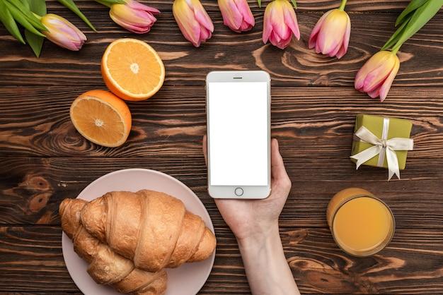 Croissant, arance, tulipani, succo di frutta, schermo vuoto del telefono. concetto di primavera