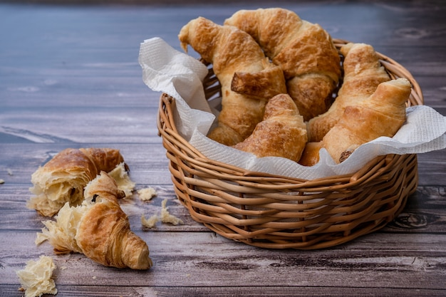 Croissant in padella o cestino del pane e parti e briciole di croissant sul tavolo.