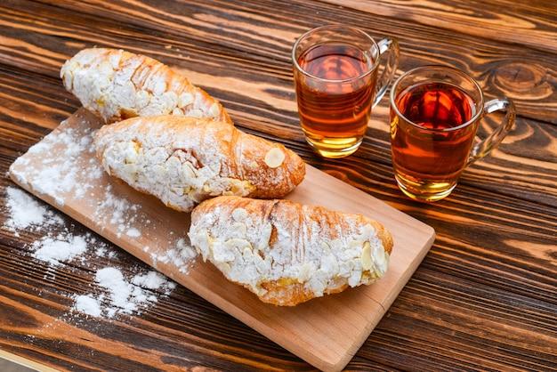 Croissant con mandorle e tè su un tavolo di legno.