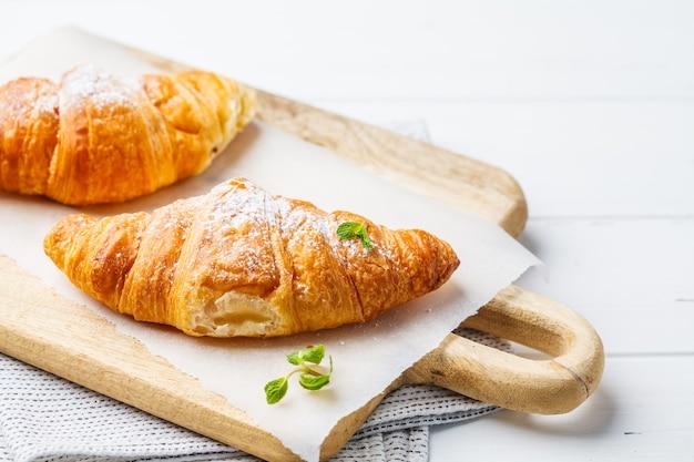 Croissant con marmellata di frutti di bosco su un fondo di legno bianco