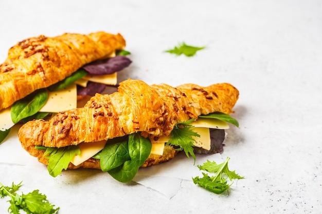 Croissant con formaggio e insalata su un fondo di legno bianco