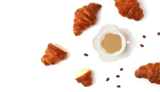 Croissant con una tazza di caffè, su uno sfondo bianco, vista dall'alto, nessun popolo, orizzontale, . foto di alta qualità