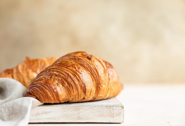 Croissant sul tagliere di legno, superficie in calcestruzzo leggero