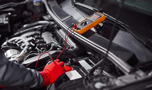 Ritaglia il tecnico anonimo in guanti protettivi che misura la tensione della batteria dell'automobile con il voltmetro durante il servizio diagnostico in officina