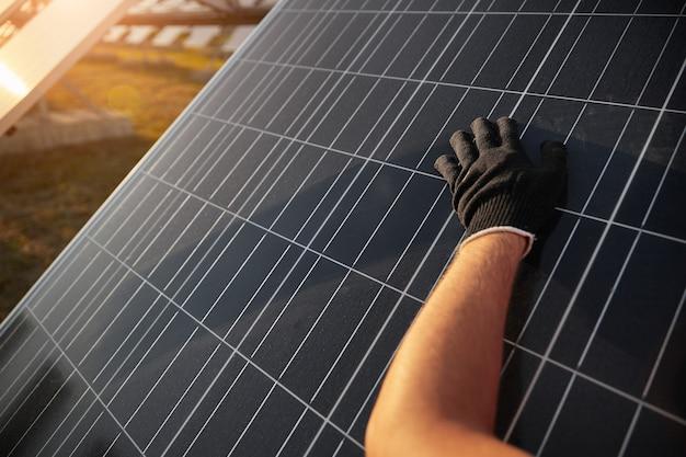 Ritaglia un operaio anonimo con un guanto nero che pulisce il pannello fotovoltaico polveroso durante i lavori di manutenzione sulla centrale solare