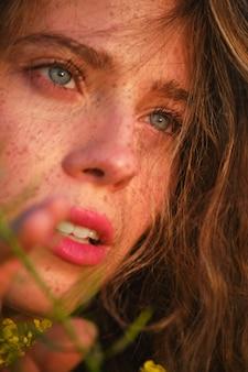 Ritaglia il viso di una donna attraente con le lentiggini