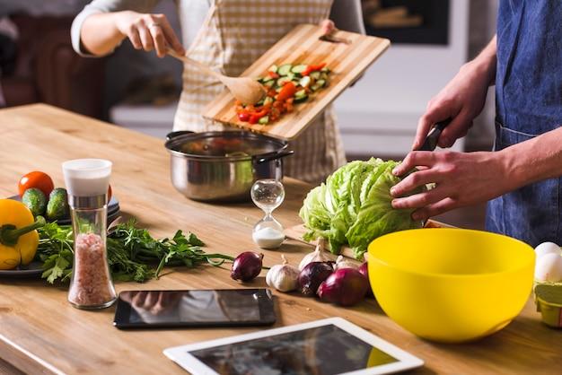 Coppie del raccolto che preparano insalata sana