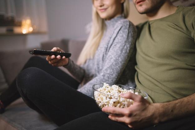 Crop coppia con popcorn guardando la tv