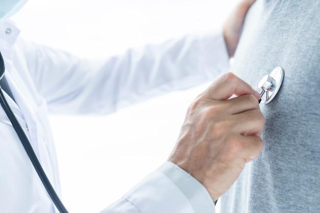 Ritaglia il dottore esaminando il torace del paziente
