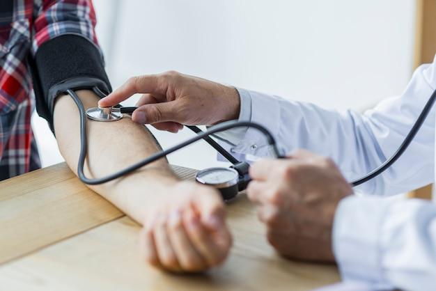 Crop dottore misurazione della pressione sanguigna del paziente