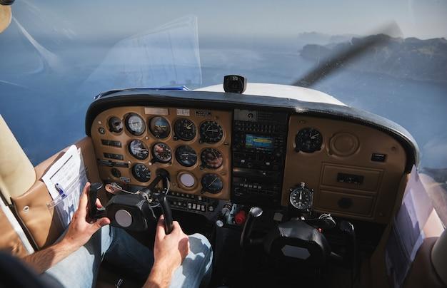 Ritaglia pilota senza volto che opera su un biplano sopra il mare blu
