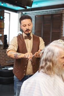 Coltivazione di capelli. barbiere barbuto serio in piedi vicino al suo cliente