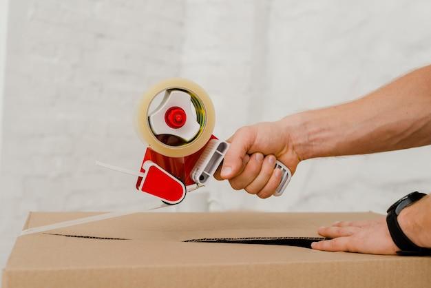 Ritaglia le mani sulla scatola di imballaggio