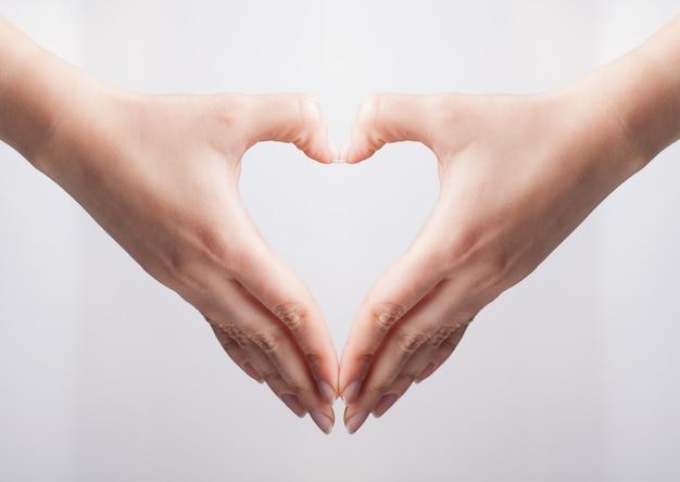 Ritaglia le mani che mostrano il gesto del cuore